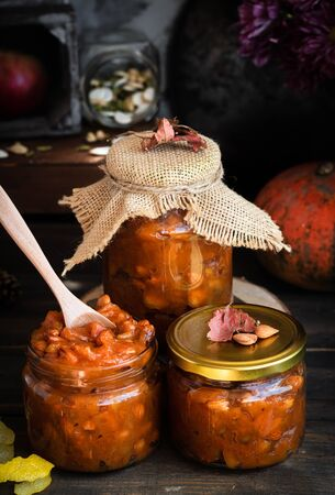 Pumpkin jam on a dark rustic background. Autumn harvest. Cozy autumn still life. Homemade preparations for the winter. Imagens - 129863350