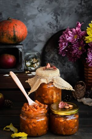 Pumpkin jam on a dark rustic background. Autumn harvest. Cozy autumn still life. Homemade preparations for the winter. Imagens - 129863381
