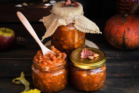 Pumpkin jam on a dark rustic background. Autumn harvest. Cozy autumn still life. Homemade preparations for the winter.