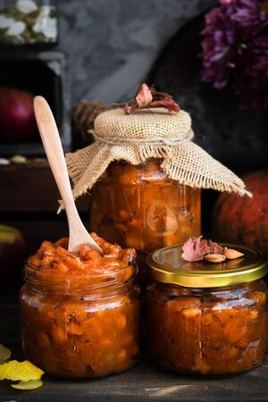Pumpkin jam on a dark rustic background. Autumn harvest. Cozy autumn still life. Homemade preparations for the winter. Imagens - 129863386