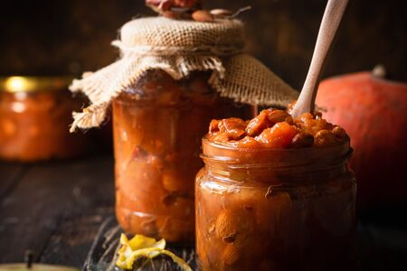 Pumpkin jam on a dark rustic background. Autumn harvest. Cozy autumn still life. Homemade preparations for the winter. Imagens - 129863387