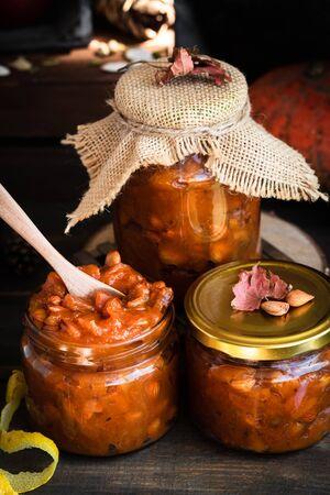 Pumpkin jam on a dark rustic background. Autumn harvest. Cozy autumn still life. Homemade preparations for the winter. Imagens - 129863388