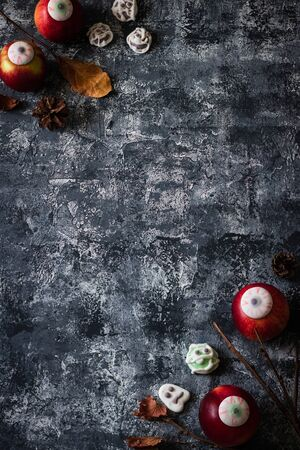Creative Halloween background with themed marshmallows and apples. Place for text.