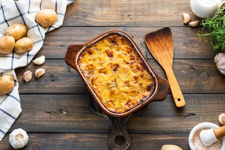 Potato casserole with garlic and rosemary. Simple and tasty food. Village lunch. Фото со стока
