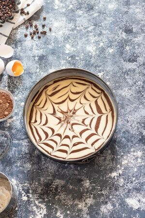 Raw dough for a sweet zebra pie in a baking dish and ingredients for it. Cooking process.