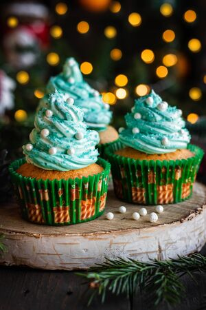 Mandarin cupcakes with festively decorated caps from butter cream. New Year and Christmas dessert.