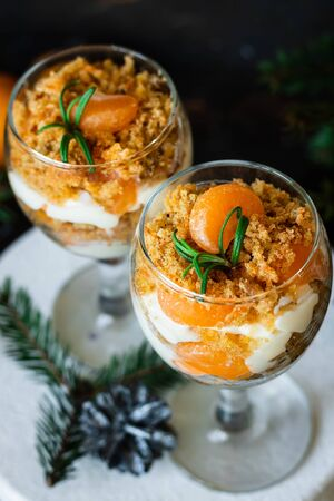 Citrus trifle with carrot biscuit and fresh tangerines in a glass. Christmas portioned dessert on the festive table.
