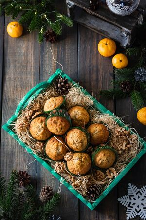 Muffins with walnuts and tangerines on a dark background. New Year and Christmas baking.