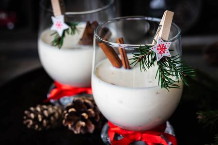 A traditional eggnog Christmas drink in a glass goblet decorated with New Year clothespin. Non-alcoholic option. Atmospheric photos.