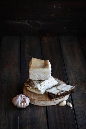 Salted pork lard on a dark wooden background.