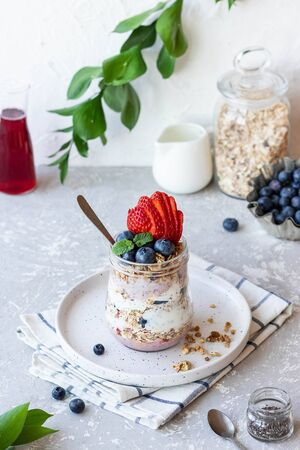 Yogurt pudding with chia seeds, homemade granola and fresh berries in a glass jar. Light snack. Healthy breakfast option.