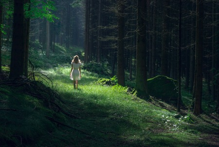 Beautiful young woman wearing elegant white dress like a fairy standing in the forest with rays of sunlight beaming through the leaves of the trees