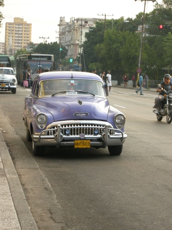 purple car: purple car driving in Havana, Cuba Editorial