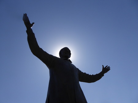 Statue of Nelson Mandela with the sun behind him, giving a halo effect Editorial
