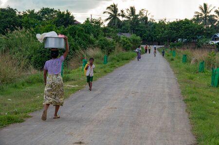 Mrauk-u, Rakhine State / Myanmar - October 18 2016: Local people on a village road at late afternoon
