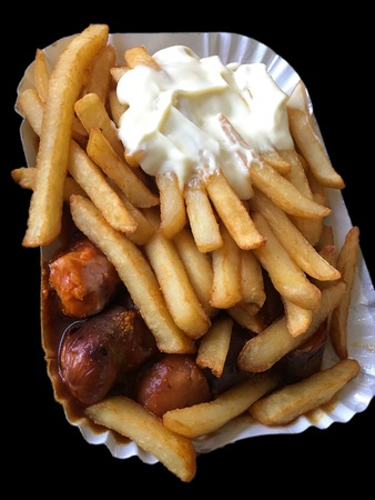 Currywurst & Pommes on black background: Famous German Fast Food (Curry Sausage with French Fries and Curry Sauce) with ketchup and mayonaise