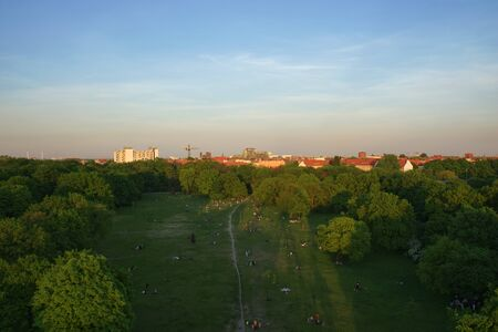 Aerial View of Berlin Park Hasenheide in Kreuzberg on an Spring afternoon with people relaxing and having fun on a large meadow in the sun. Behind the trees you can see roof tops of Berlin. Stok Fotoğraf