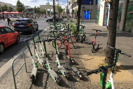 BERLIN - SEPTEMBER 08, 2019: Many Electric E-Scooters of different Ride Sharing Companies parked chaoticly on a sidewalk in Berlin close to the Brandenberg Gate. Modern and trendy City Transport