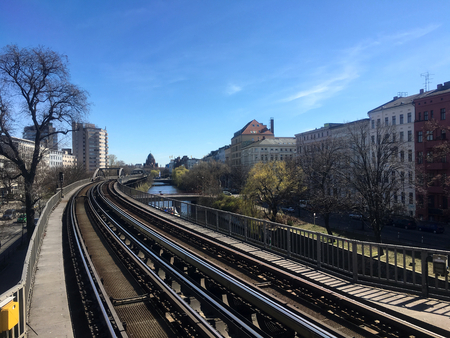 Metro Train (U-Bahn) Tracks going through Berlin next to Landwehrkanal and Houses in sunny spring weather with blue sky. Berlin Public Transportation is one of the best in Europe and Eco-friendly. Editöryel
