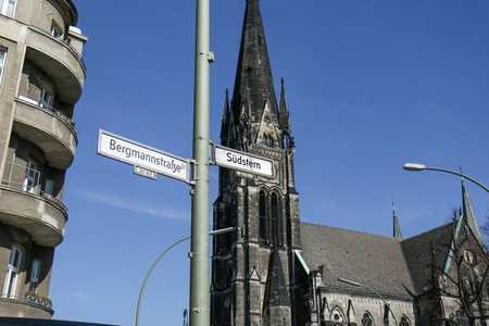 BERLIN - MARCH 3, 2014: Street Signs of South Star and Hasenheide with gothic church in the background on a clear sunny day