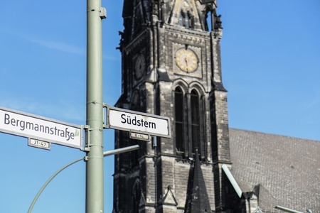 BERLIN - MARCH 3, 2014: Street Signs of Südstern and Hasenheide with gothic church in background on a clear sunny day Editöryel
