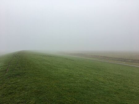 A Dyke in the Mist on a foggy day in East Frisia, in the North of Germany near Pilsum. Northsea coast.