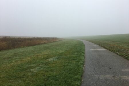 A path / road along a Dyke in the Mist on a foggy day in East Frisia, in the North of Germany near Pilsum. Northsea coast.