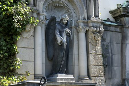 Sculpture of an Angel with flowers (roses) in her hand on a family tomb / crypt at the cemetery at Suedstern Editöryel