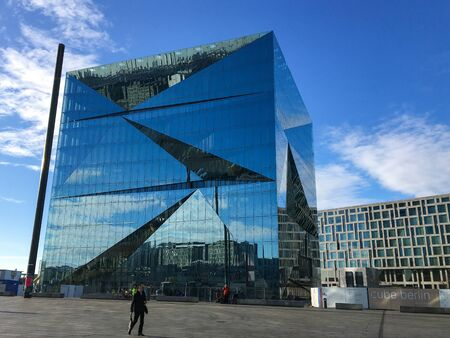 BERLIN - JANUARY 21, 2020: Cube Berlin, a modern and futuristic office building next to Central Station at Washingtonplatz. Part of Europacity. City and sky reflecting in the glass facade.