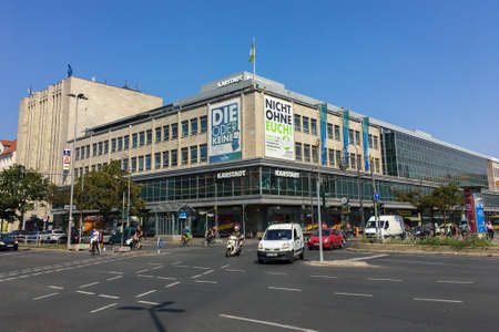 BERLIN, GERMANY - AUGUST 08, 2020: Karstadt Department Store at Hermannplatz in the summer with cars passing by. Karstadt Warenhaus GmbH is a German department store chain.