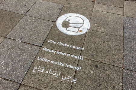 Sign saying Please wear a mask painted on pavement/sidewalk of Shopping Street to stop spreading Corona Virus Editöryel