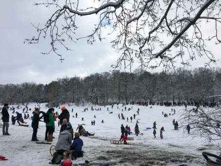 BERLIN, GERMANY - JANUARY 30, 2021: People enjoying the snow in the city at public park Hasenheide. Families with children on selsdges having fun in the snow. Some wearing masks because of the corona pandemic. Editöryel