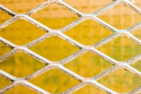 Metallic Fence in a Yellow Background Stock Photo