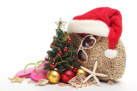 Santa Claus hat and Christmas tree with beach accessories on white background.