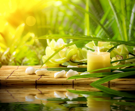 still water: candle, pebble stones and orchid on bamboo mat Stock Photo