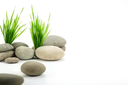 Zen stone with fresh grass on white background
