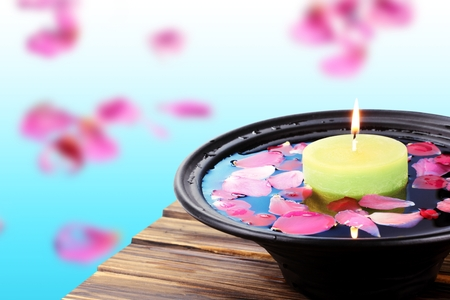 Spa  still life with candle and rose petals over bright background. Reklamní fotografie
