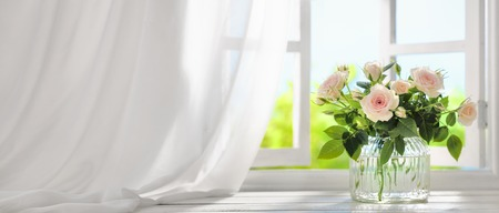 Bouquet of rose flowers near window with curtain