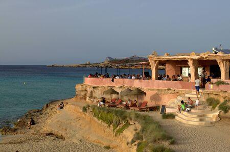 People drinking at the beach bar in Cala Conta, Ibiza, Spain.