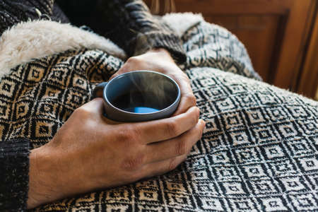 Close up of male hands holding warm coffee while sitting on sofa.