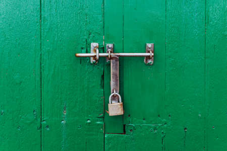 Green wooden gate closed with a padlock. Closed door concept ..