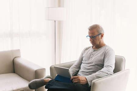 Old man in casual wear is looking a digital tablet in the living room. 版權商用圖片 - 166318394