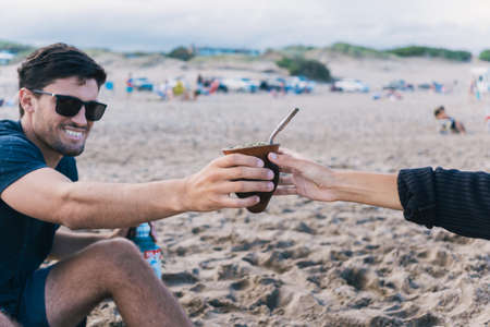 Young man sharing mate with a girl at the beach.