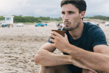 Attractive young man drinking yerba mate alone at the beach.