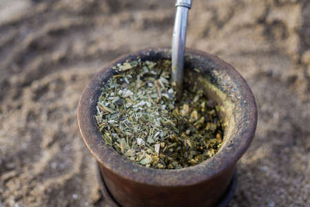 Detail of Yerba mate dry leafs in calabash with bombilla, popular drink in Latin America. 版權商用圖片