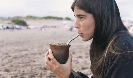 Young woman drinking traditional Argentinian yerba mate herbal tea at the beach. 版權商用圖片