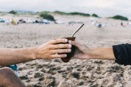Close up image of a girl and a boy hands sharing yerba mate at the beach