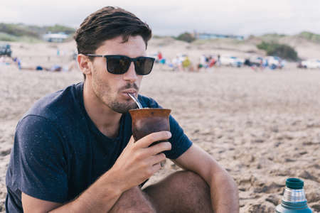 Handsome young man drinking mate at the beach.