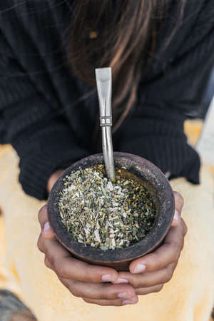 Traditional argentinian yerba mate tea in a calabash gourd with bombilla stick.