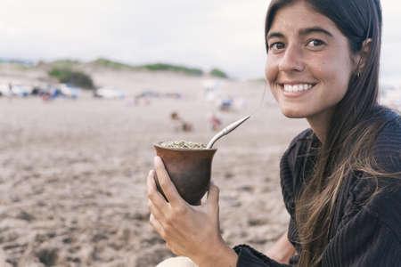 Beautiful young woman drinking traditional yerba mate tea.
